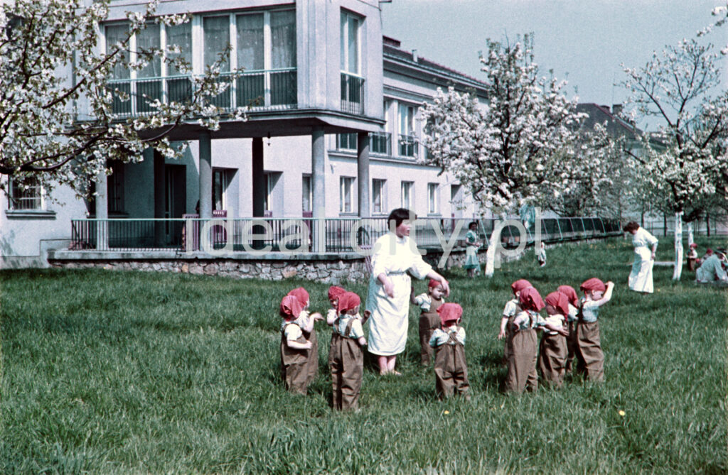 On the green lawn, the babysitter stretches out her arms to the surrounding small children in red headscarves, in the background a two-story pavilion.