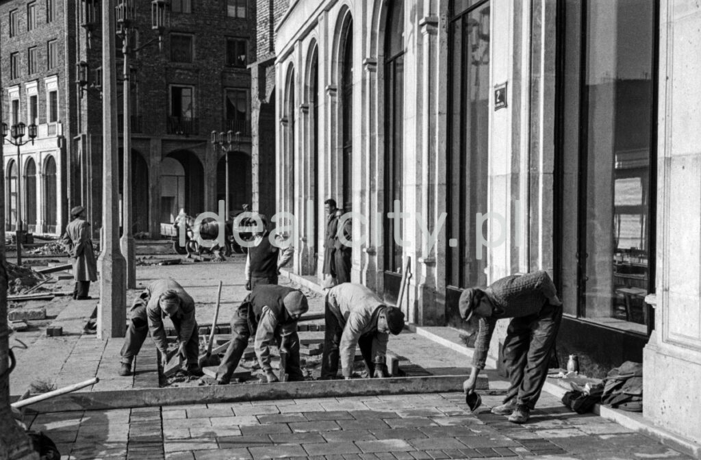 Workers are laying paving slabs in front of the monumental building.