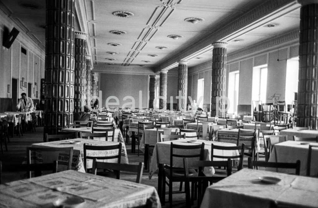 A perspective on the monumental interior of the restaurant. On the sides of the column, a few customers and a waiter in the background.