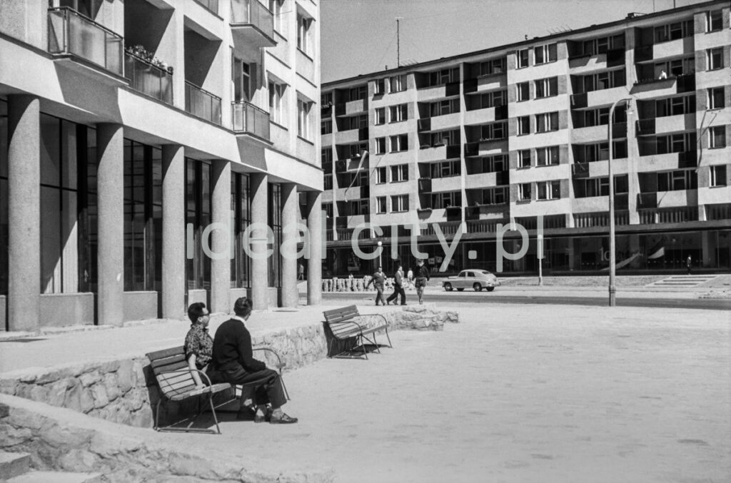 Two men sit on a bench between modernist blocks.