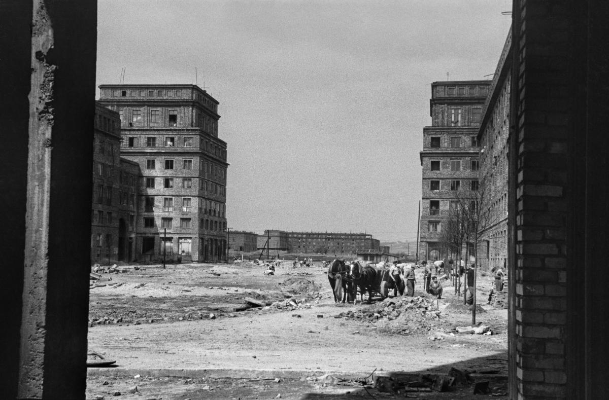 Widok na plac miejski w budowie, po lewej i prawej stronie monumentalna zabudowa. Pośrodku wóz konny w trakcie rozładunku materiałów budowlanych.