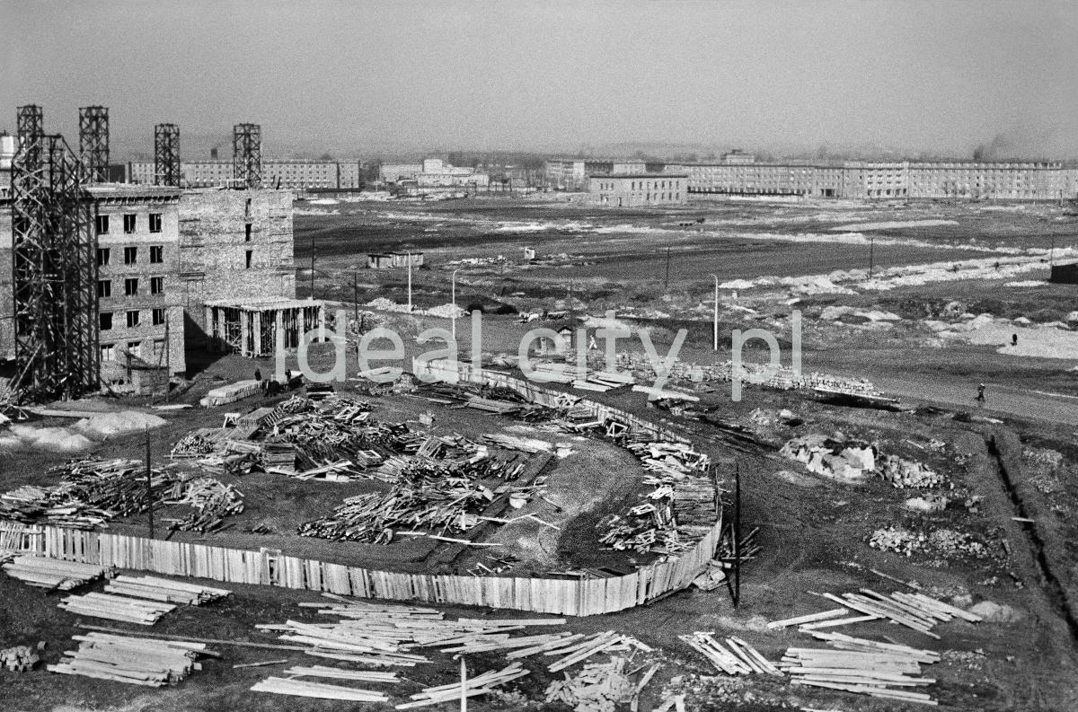 Widok z wysokości na plac budowy okrążony nierównym płotem. Z lewej i w dalekiej perspektywie - budowa domów.