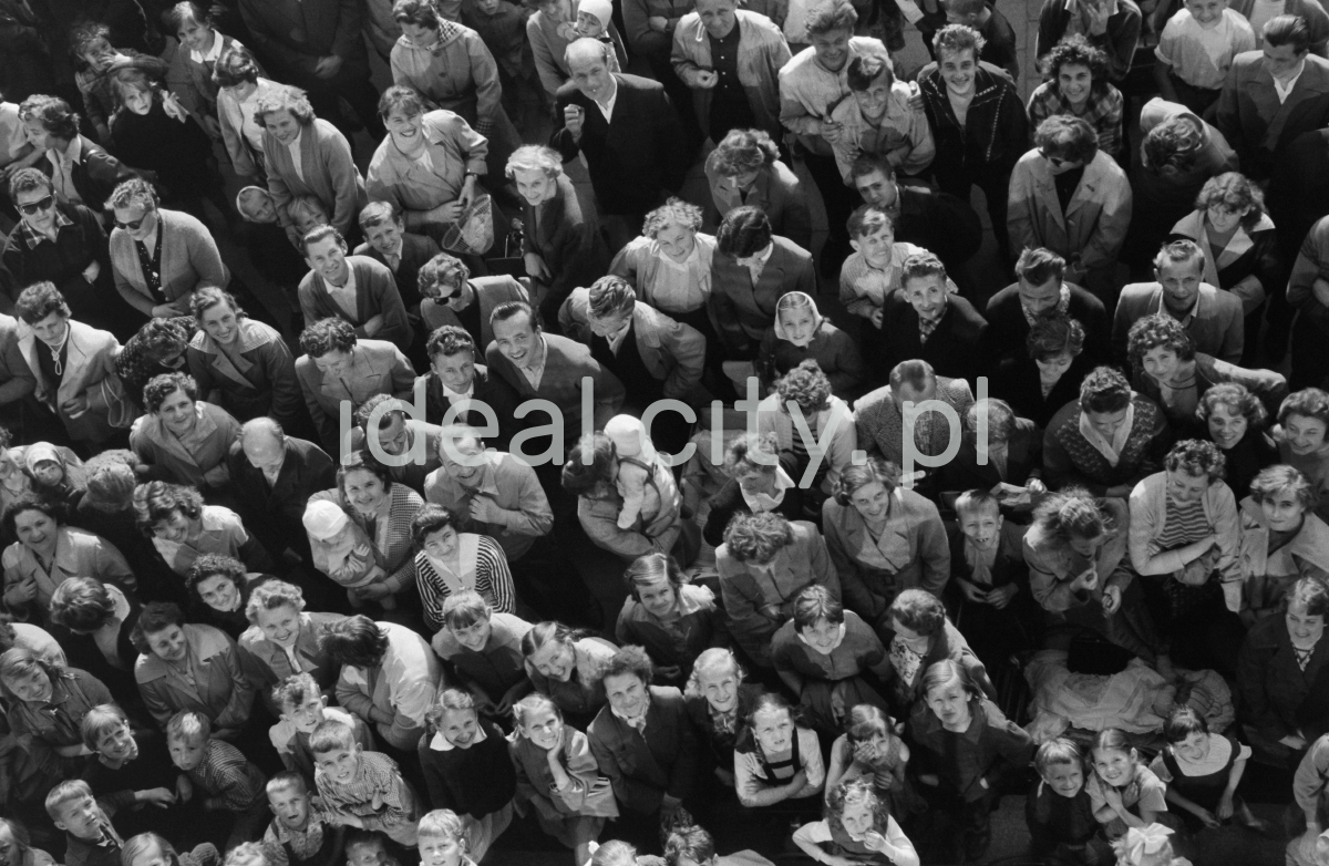 Widok z góry na tłum zgromadzony przed wejściem do budynku. Część z osób patrzy w obiektyw.