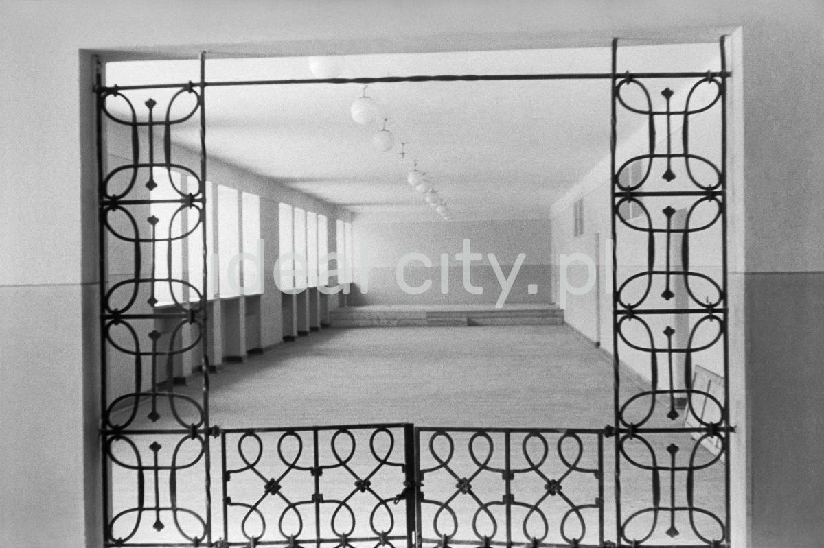 Widok przez wewnętrzną kratę na pusty korytarz szkolny.