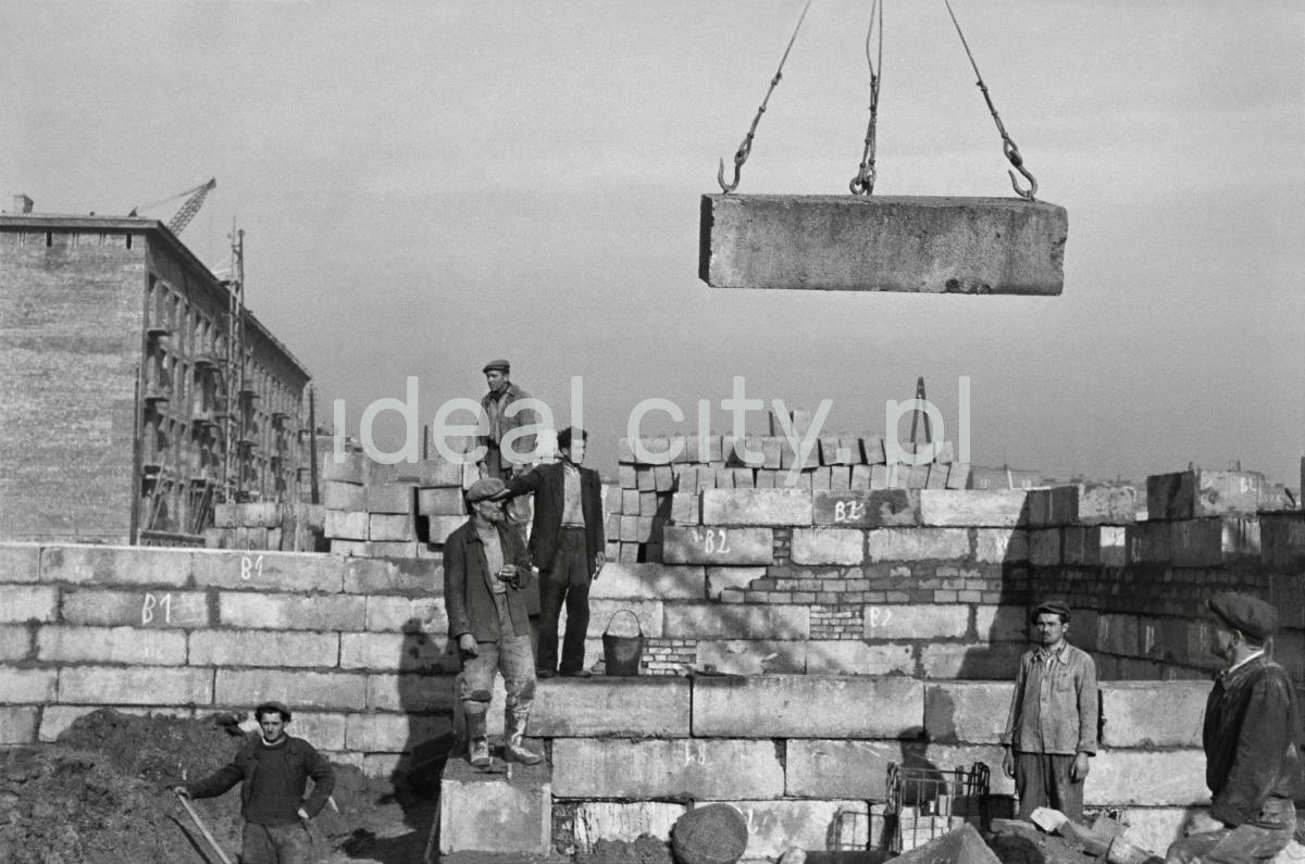 Ekipa robotników odbiera transportowaną przez dźwig betonową płytę. Dookoła plac budowy,