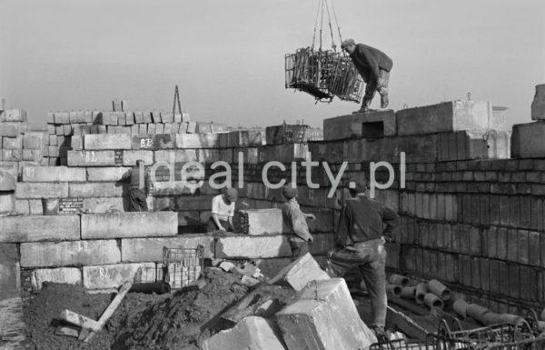 Ekipa robotników w trakcie odbioru materiałów transportowanych za pomocą dźwigu.