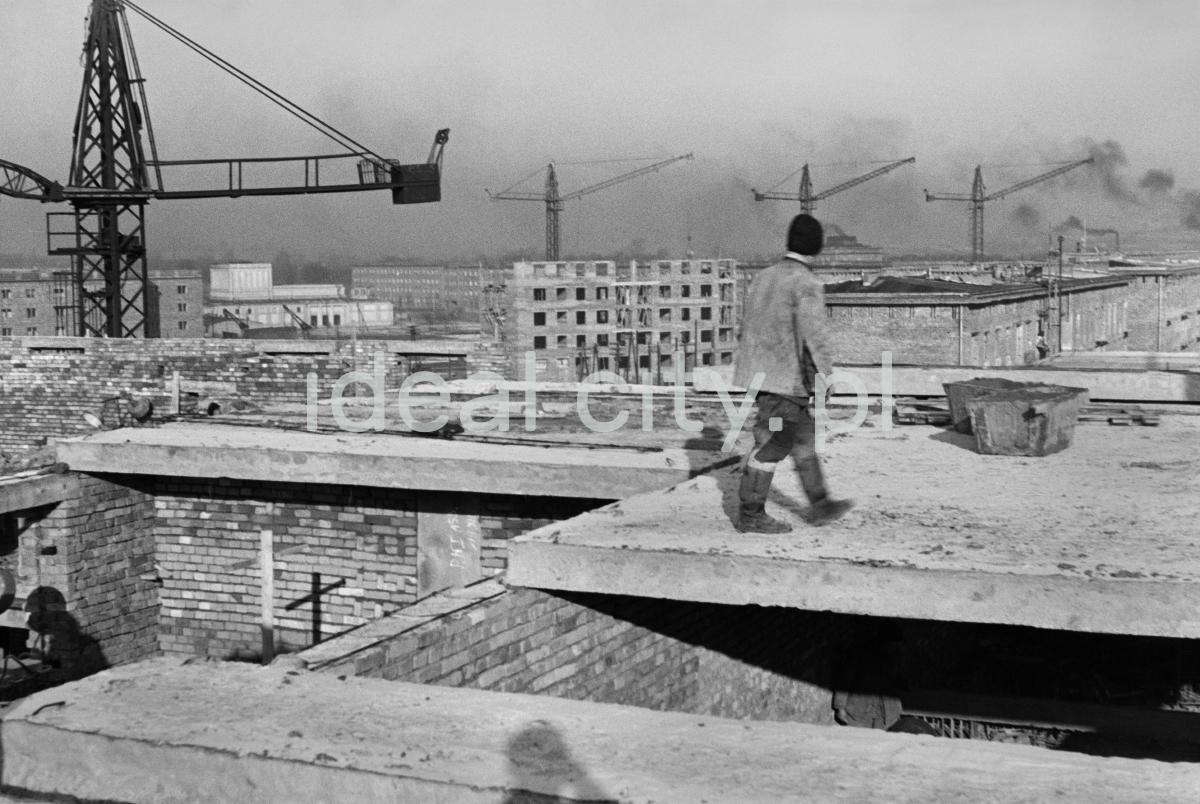 Robotnik na nowo budowanej płycie kondygnacji budynku.