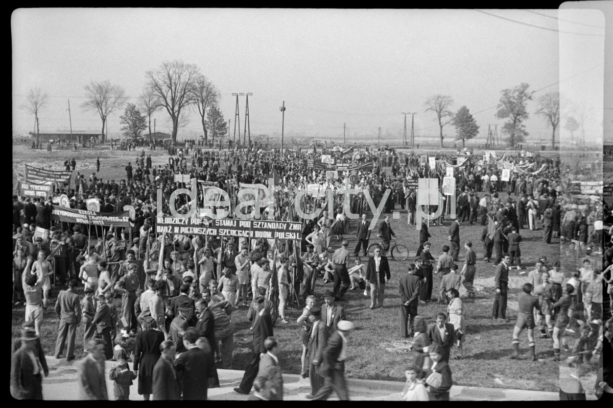 Tłum na placu z transparentami pierwszomajowymi, dookoła łąki.