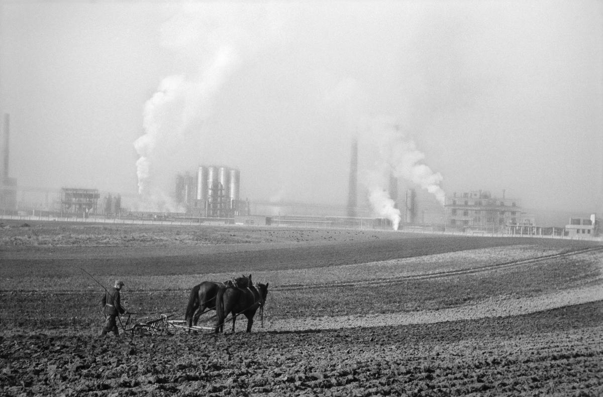 Rolnik orze ziemię pługiem zaprzągniętym w dwa konie, w tle dymiące kominy kombinatu.