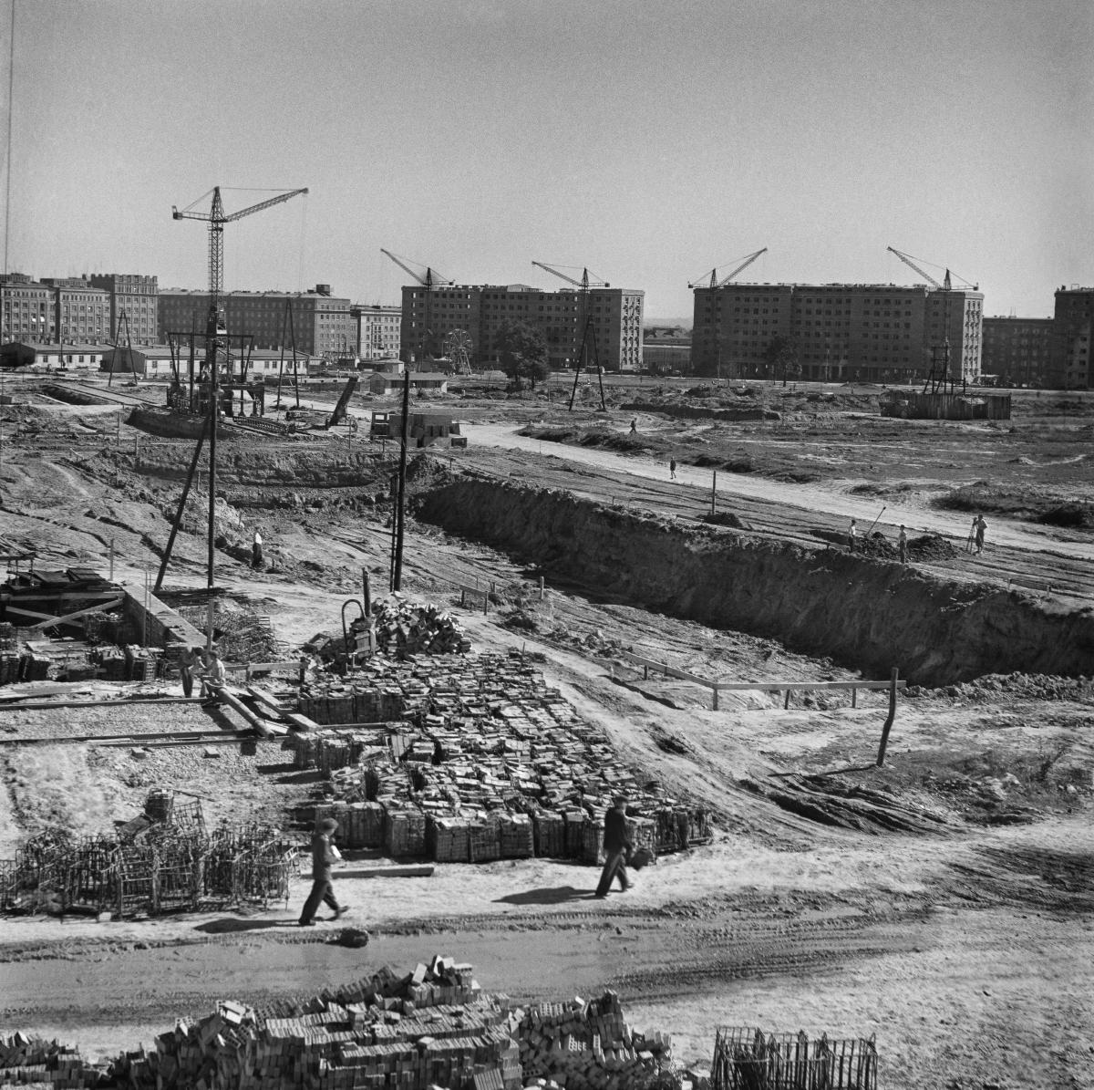 Widok na teren budowy. Na pierwszym planie koszyki cegieł, dalej głęboki wykop, w dali zabudowa blokowa oraz dżwigi budowlane.