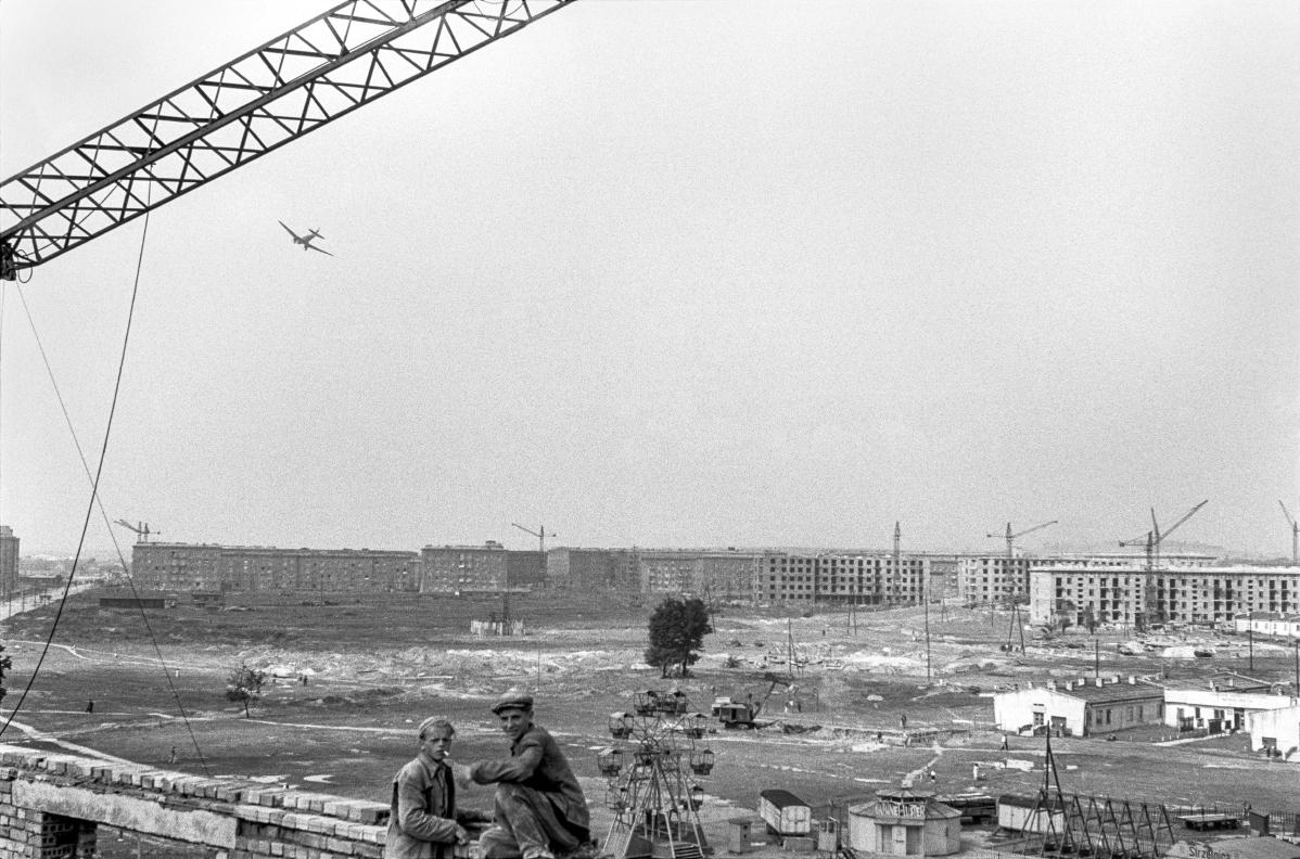 Panorama na budowę osiedlii. Na pierwszym planie dwóch robotników, po lewej fragment dźwigu, w głębi zabudowa mieszkaniowa, na niebie samolot.