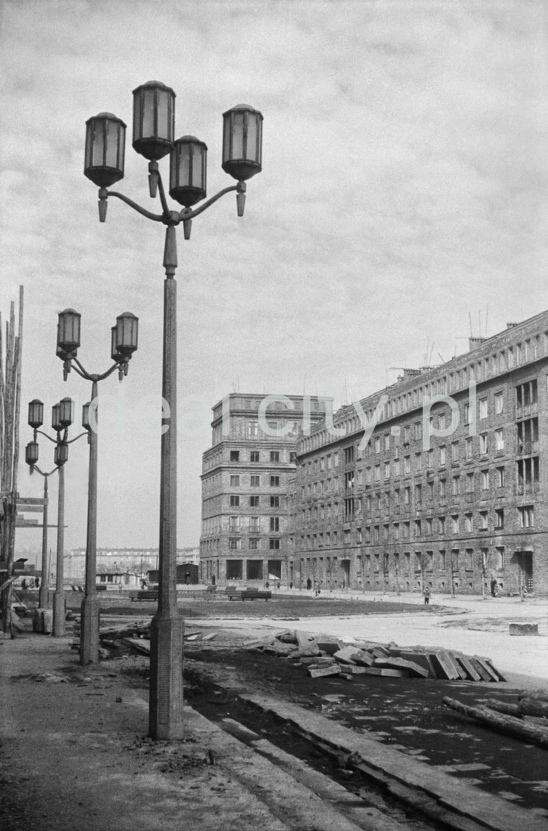 Pionowe ujęcie na reprezentacyjny plac miejski otoczony monumentalnymi budynkami mieszkalnymi w stylu socrealistycznym, na pierwszym planie utrzymane w konwencji latarnie miejskie