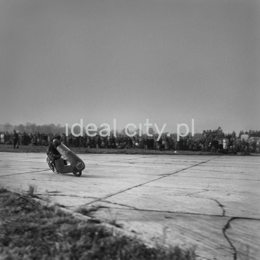 Przechylony motocyklista pędzi po płytach pasa startowego. W tle tłum gapiów.