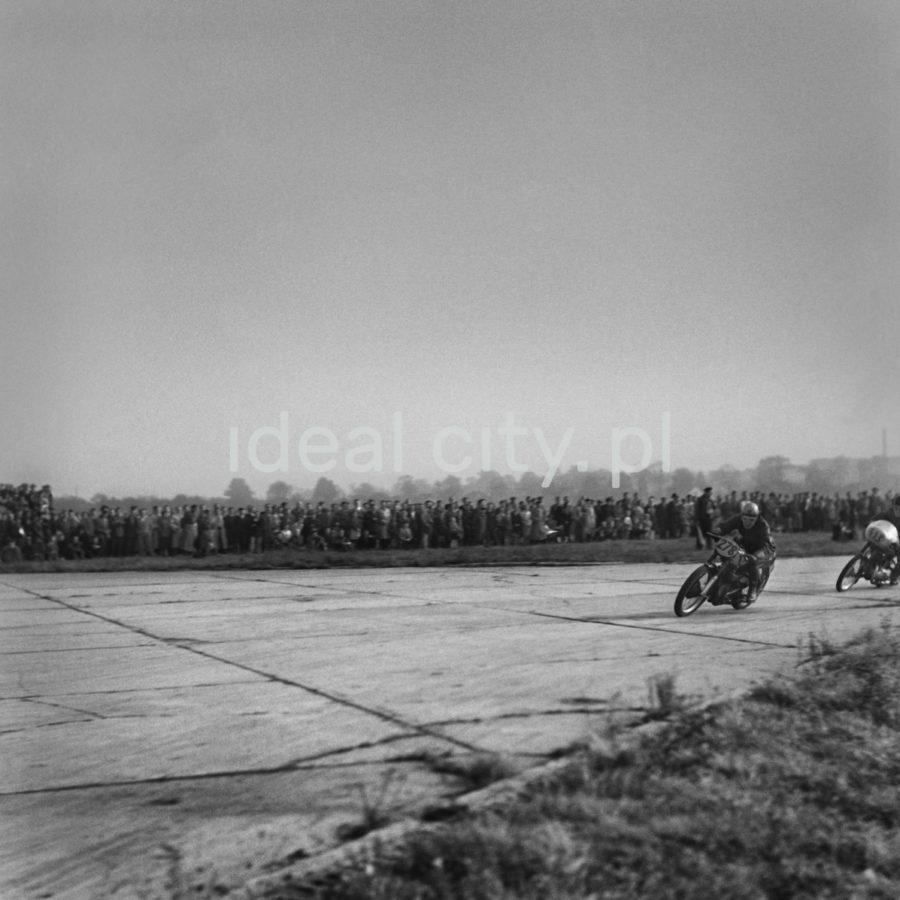 Dwóch motocyklistów pędzi w stronę kamery po płytach pasa startowego. W tle tłum gapiów.