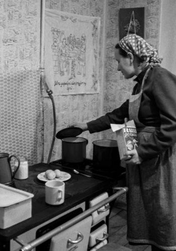 Kobieta w fartuchu przygotowuje posiłek przy kuchni węglowej. W ręku trzyma płatki owsiane, na blacie garnki, talerz z jajkami. Podnosi pokrywkę jednego z garnków.