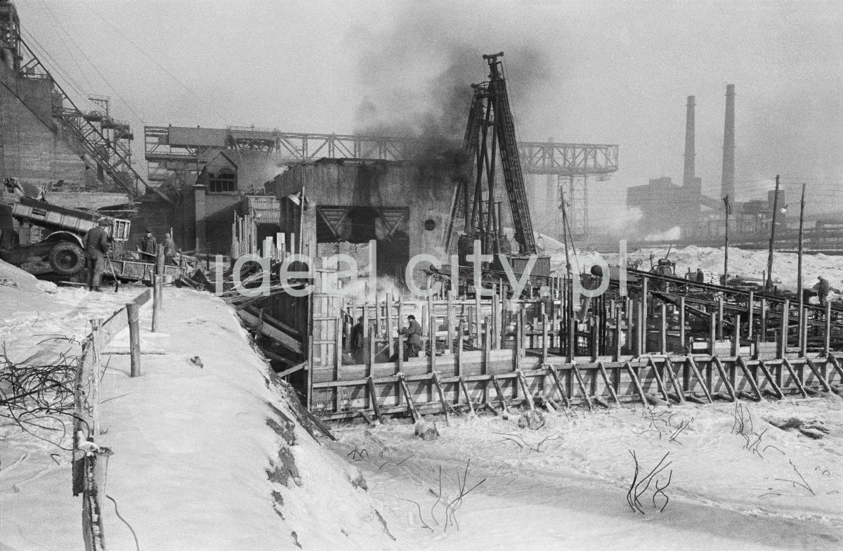 Zimowe ujęcie na elementy konstrukcyjne w trakcie budowy, w tle kominy.