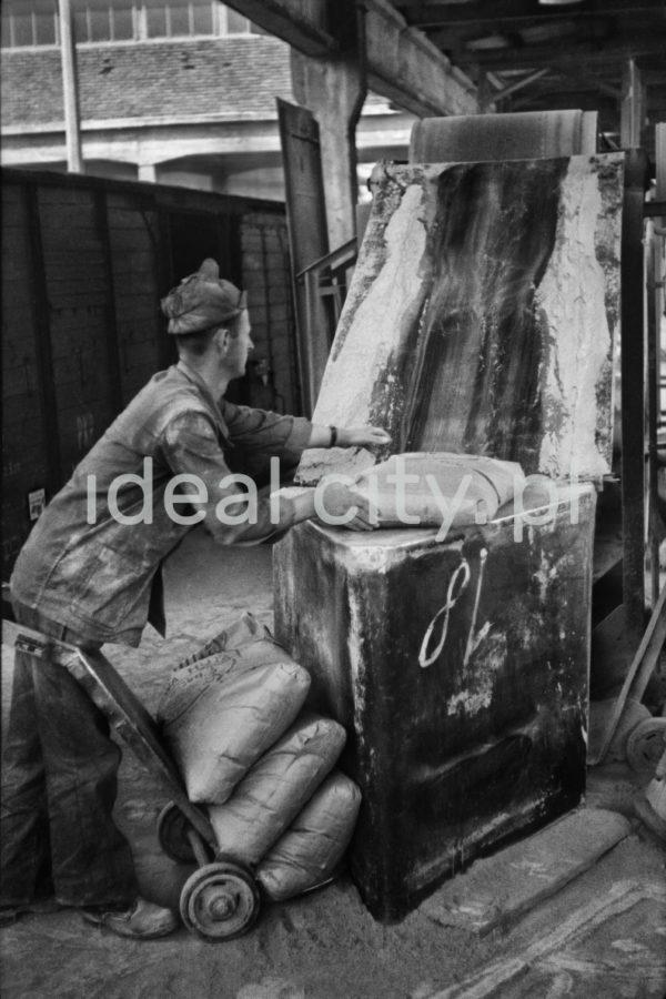Mężczyzna w zabrudzonym ubraniu roboczym napełnia przy taśmociągu worki sypkim materiałem.