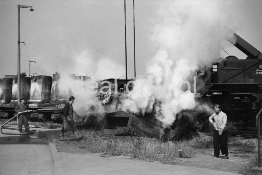Mężczyzna na tle spowitych parą wagonów, obok postać z sikawką do gaszenia pożarów.