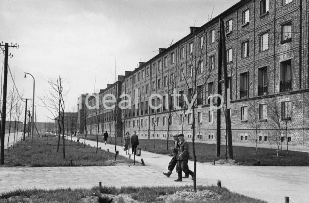 Ruch pieszy na chodniku przed ciągie nieotynkowanych trzypiętrowych budynków mieszkalnych z cegły. Na pierwszym planie przechodzi dwóch mężczyzn w roboczych kufajkach i gumofilcach.