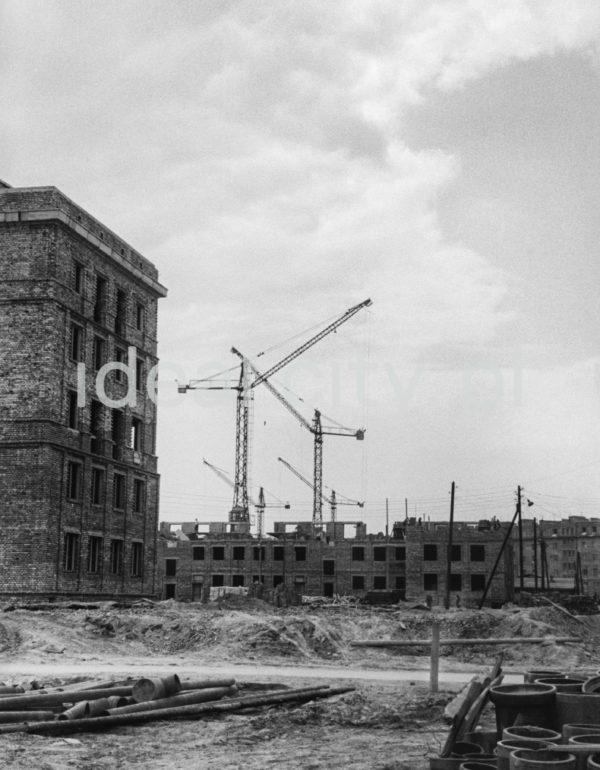 Widok na plac budowy, żurawie. Po lewej trzypiętrowy budynek z cegły.