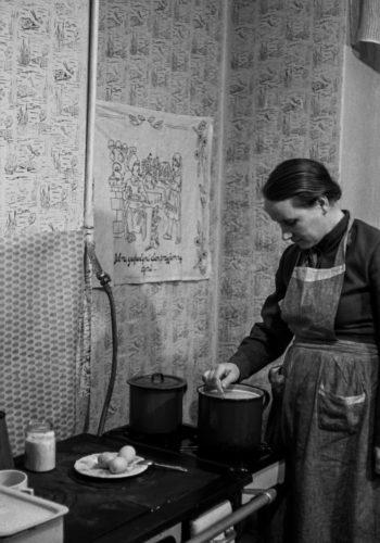 Kobieta w fartuchu przygotowuje posiłek przy kuchni węglowej. Na blacie garnki, talerz z jajkami.