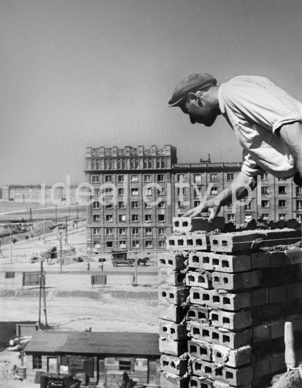 Murarz układa cegły stoją na rogu wyższej kondygnacji budynku.