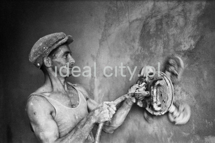 Mężczyzna w kaszkiecie i podkoszulku na ramiączkach szlifuje sprzętem mechanicznym ścianę uśmiechając się przy tym.