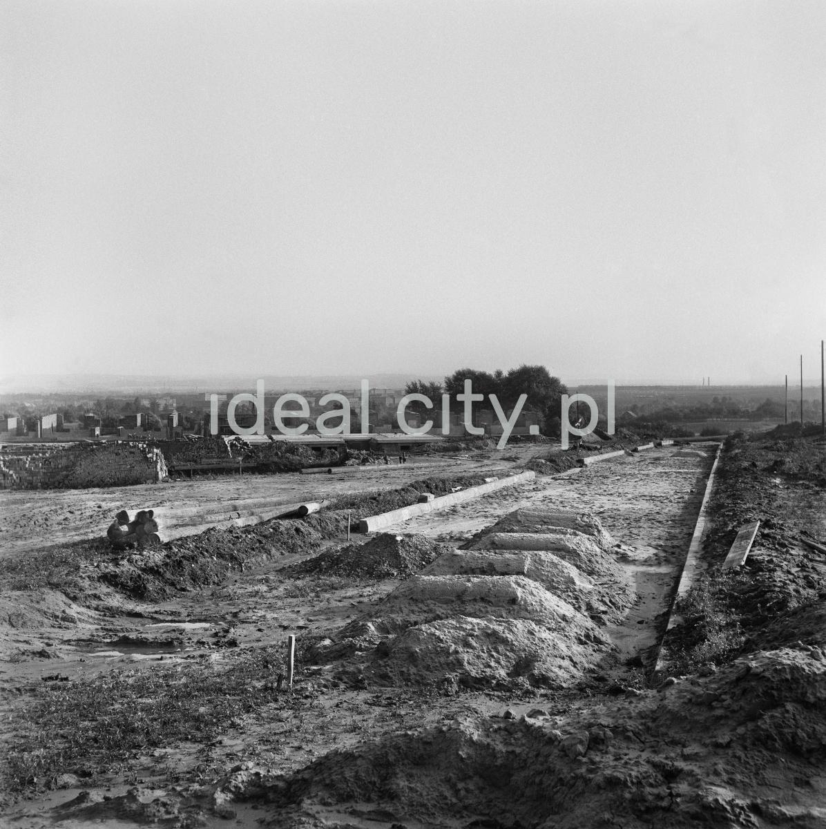 Plac budowy na otwartej łące, w dalekiej perspektywie widoczne zabudowania i kominy.