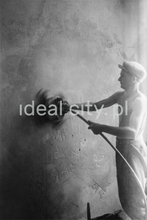 Mężczyzna w kaszkiecie i podkoszulku na ramiączkach szlifuje sprzętem mechanicznym ścianę.