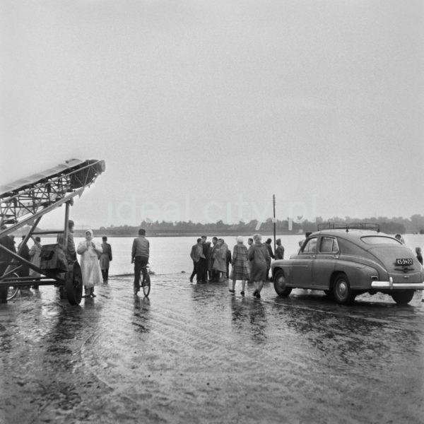 Postaci oraz samochód w deszczowy dzień na schodzącej w stronę rzeki drodze.