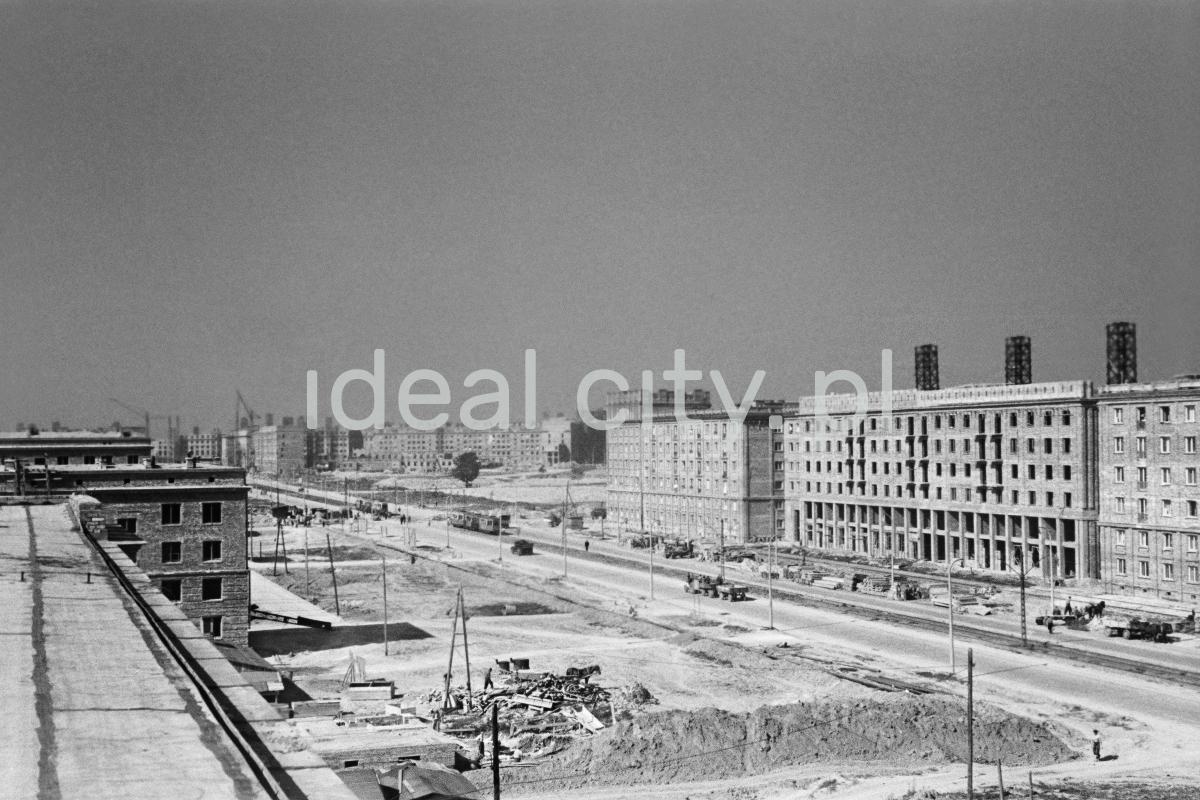 Widok panoramiczny z wysokości na plac budowy, w perspektywie po prawej bliskie ukończenia budynki.