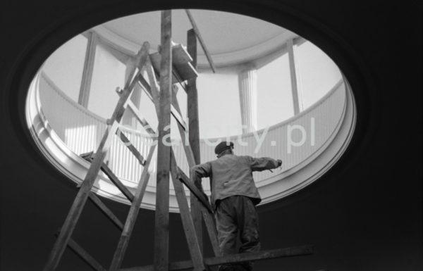 Mężczyzna w stroju roboczym, stojąc na drabinie maluje ściany okrągłego świetlika zwieńczającego halę.