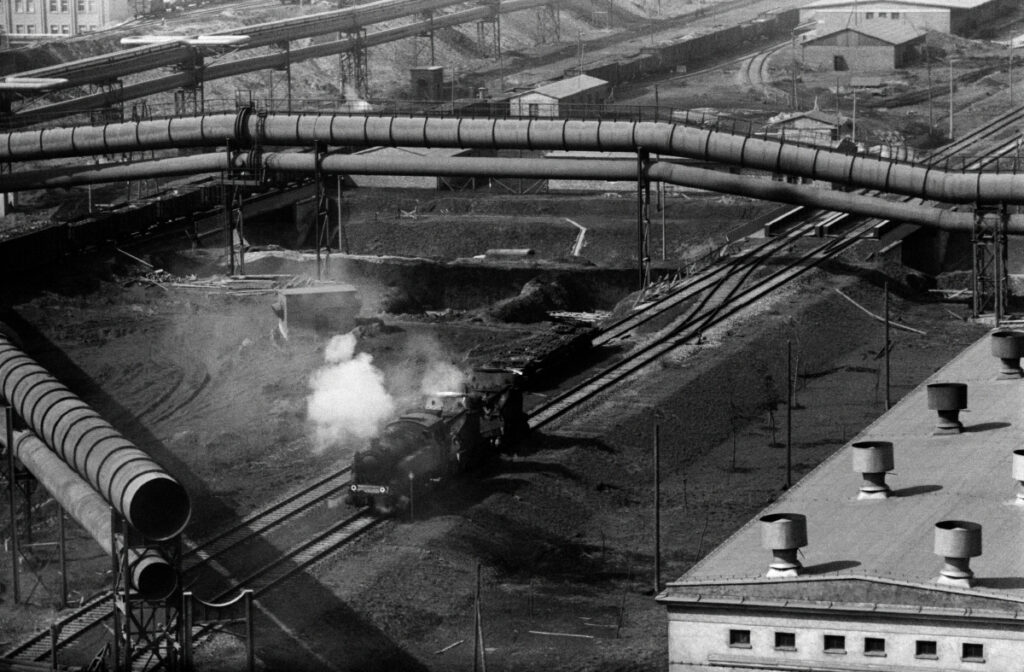 A top view of the tangle of pipelines, with a diesel locomotive passing between them.