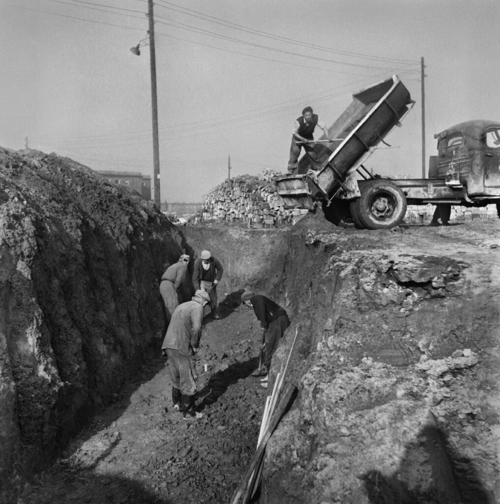 Workers work with shovels in the trench, over them is a dump truck.