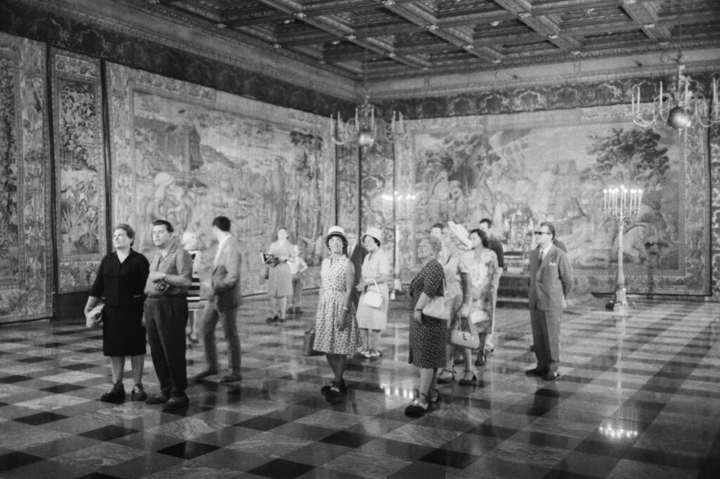 A group of tourists is examining the tapestries on the walls of a spacious room.