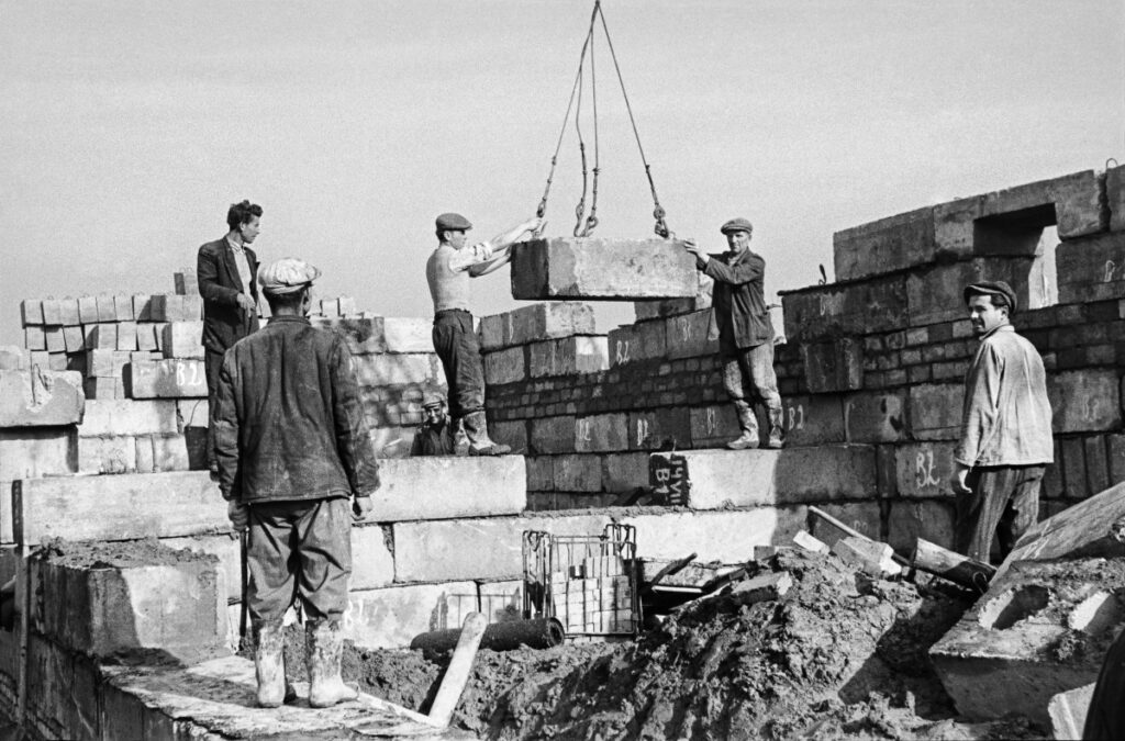 Two workers steer a concrete block fed from above by a crane, a few others watch it.