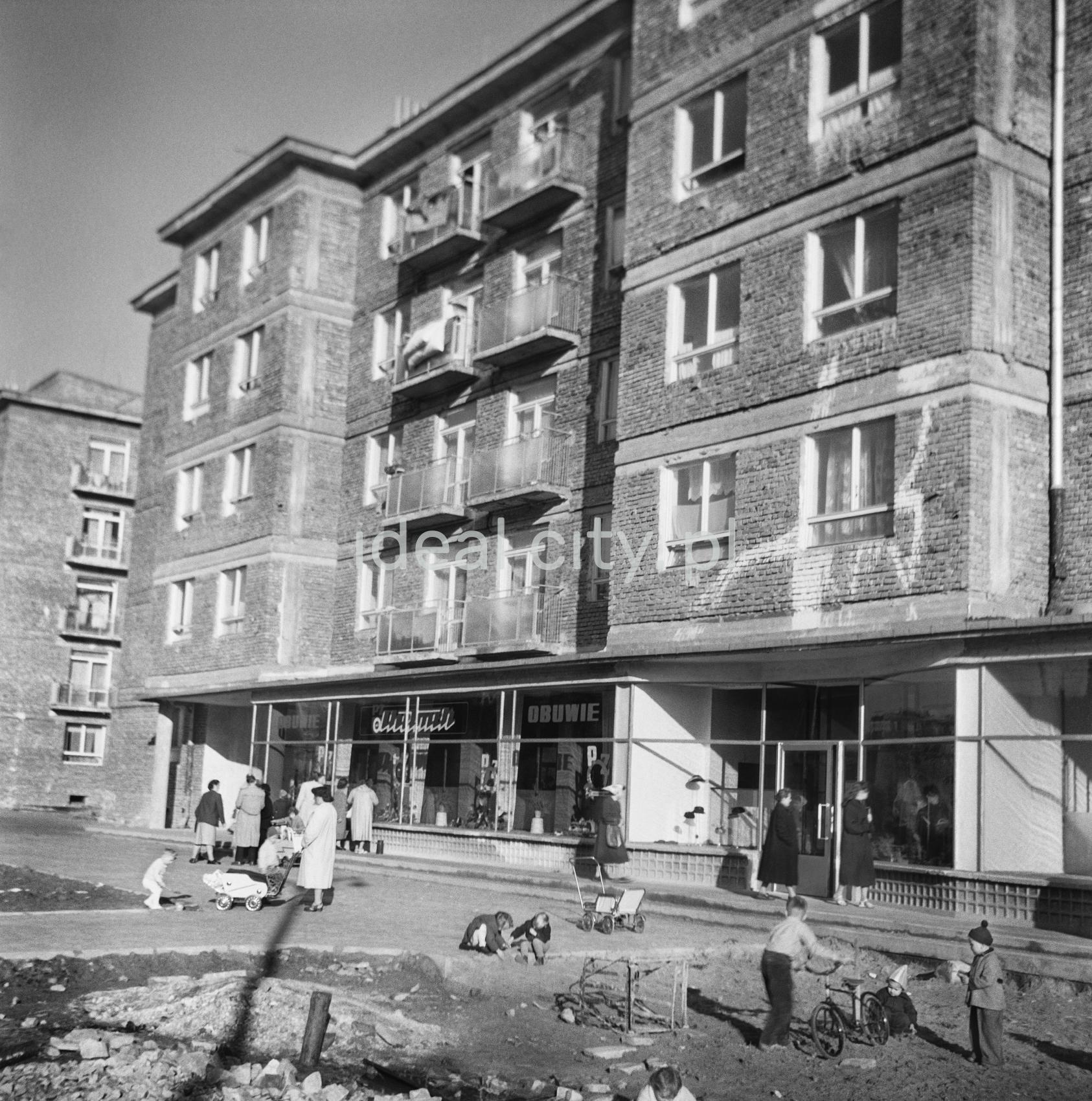 Ruch pieszy i zabawy dziecięce przed pawilonami sklepowymi na parterze nowo ukończonego bloku z cegły.