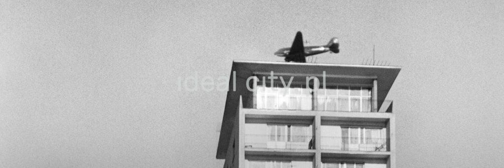 Samolot przelatuje tuż nad dachem wysokiego bloku mieszkalnego. Ujęcie z dołu.