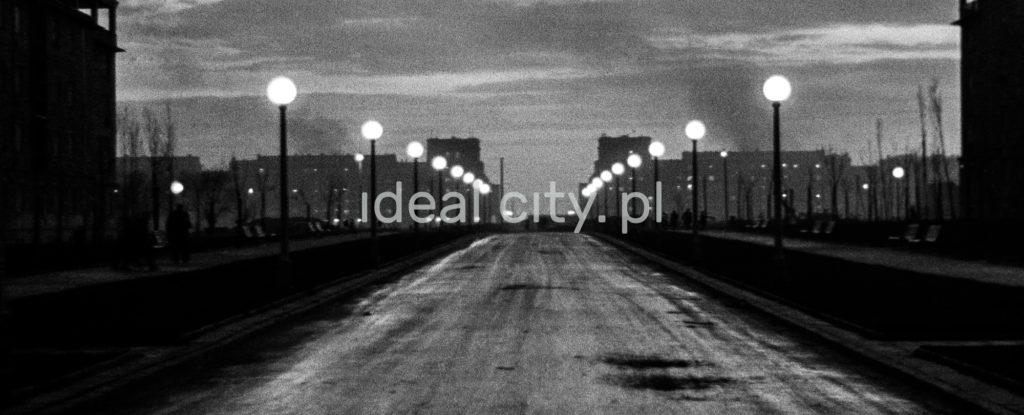 Szeroka aleja w brzasku świtu, wzdłuż święcące latarnie uliczne.