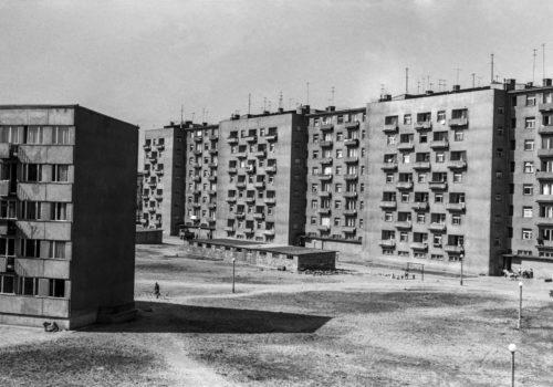 Miniaturowe postaci dziecięce oraz przedwojenny w charakterze samochód na pustkowiu pomiędzy modernistycznymi blokami osiedla Centrum D.