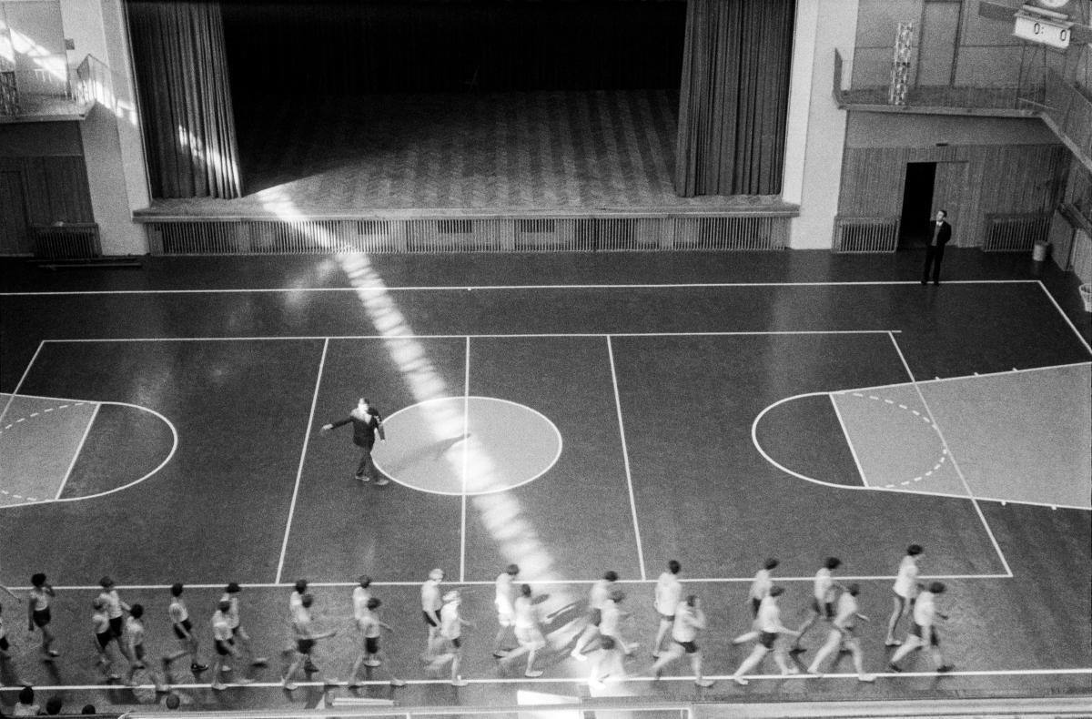 Trener zagania dzieci do biegu parami dookoła klasy gimnastycznej. Na środek sali wpada promień słońca.