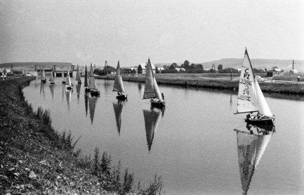 Ustawione w szeregu żaglówki płyną jedna za drugą wzdłuż rzeki.
