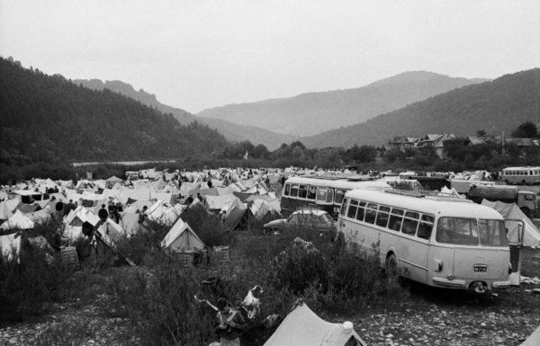Namiotowe obozowisko w dolinie nad rzeką, pomiędzy namiotami zaparkowane autobusy i auta osobowe.