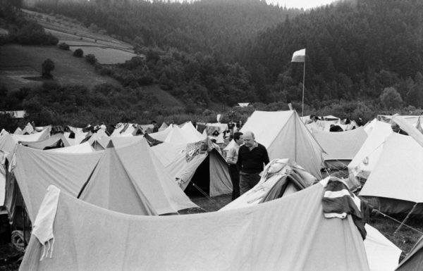 Namiotowe obozowisko w dolinie. Namioty rozstawione losowo, jednak każdy w takiej samej wielkości i kolorze.