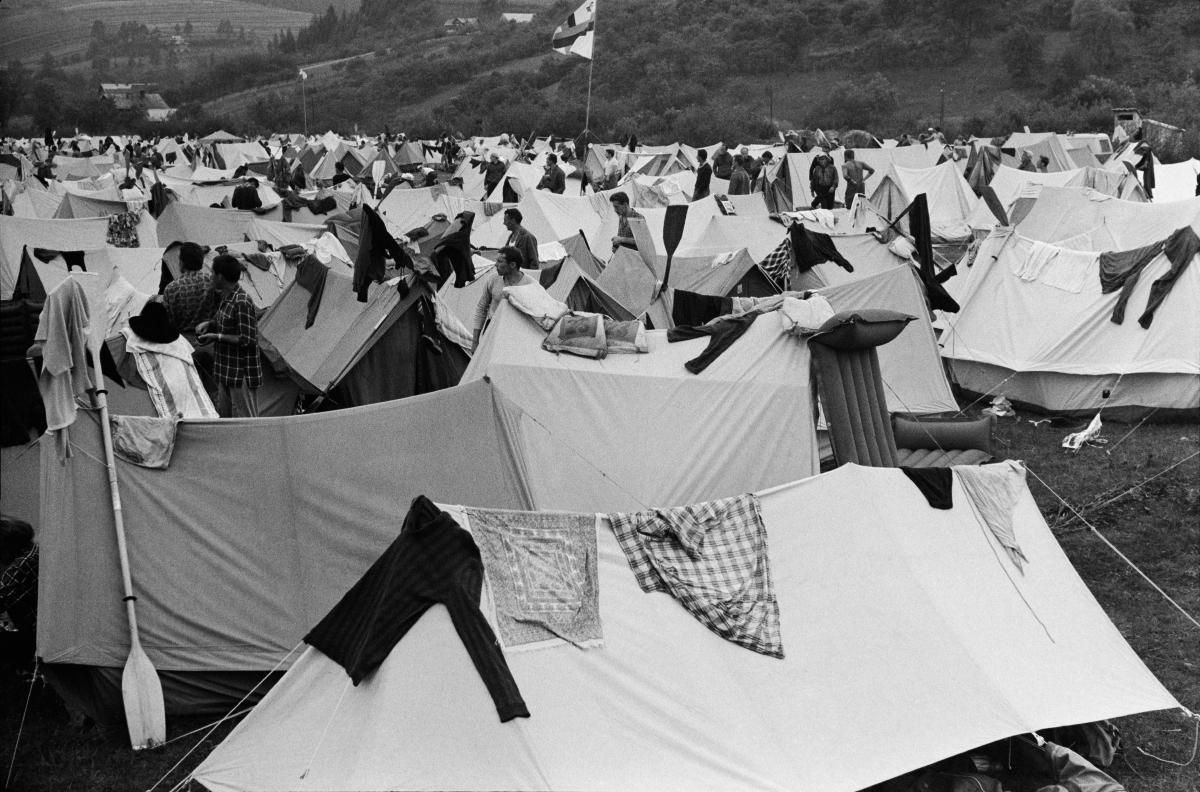 Obozowisko uczestników rajdu turystycznego. Na ciągnących się po horyzont namiotach suszą się ubrania. Gdzieniegdzie widać oparte wiosła do kajaków.