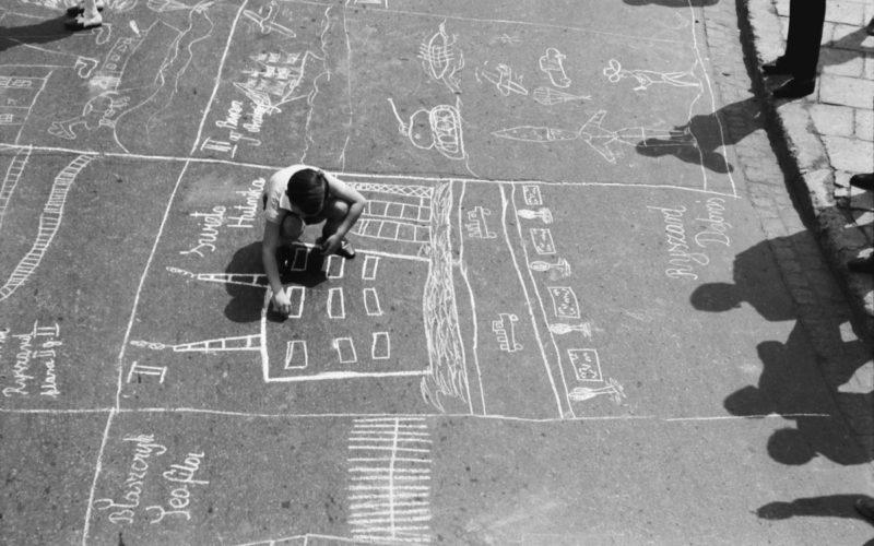 Grupa dzieci pod nadzorem dorosłych rysuje kredą na asfalcie.