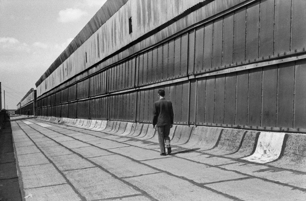 Obrócony plecami do obiektywu mężczyzna idzie wzdłuż wyłożonego arkuszami blachy tarasu nad halą fabryczną, po prawej góruje świetlik budynku, równie długi jak taras i sam budynek.