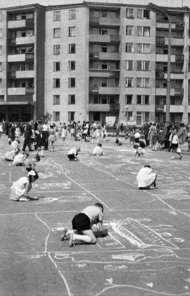 Grupa dzieci pod nadzorem dorosłych rysuje kredą na asfalcie. W tle modernistyczne bloki.