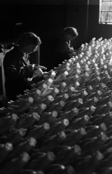Pracownica w pogrążonej w mroku hali fabrycznej maluje korpusy lalek.