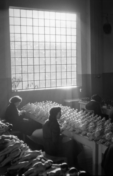 Dwie pracownice w pogrążonej w mroku hali fabrycznej malują korpusy lalek.